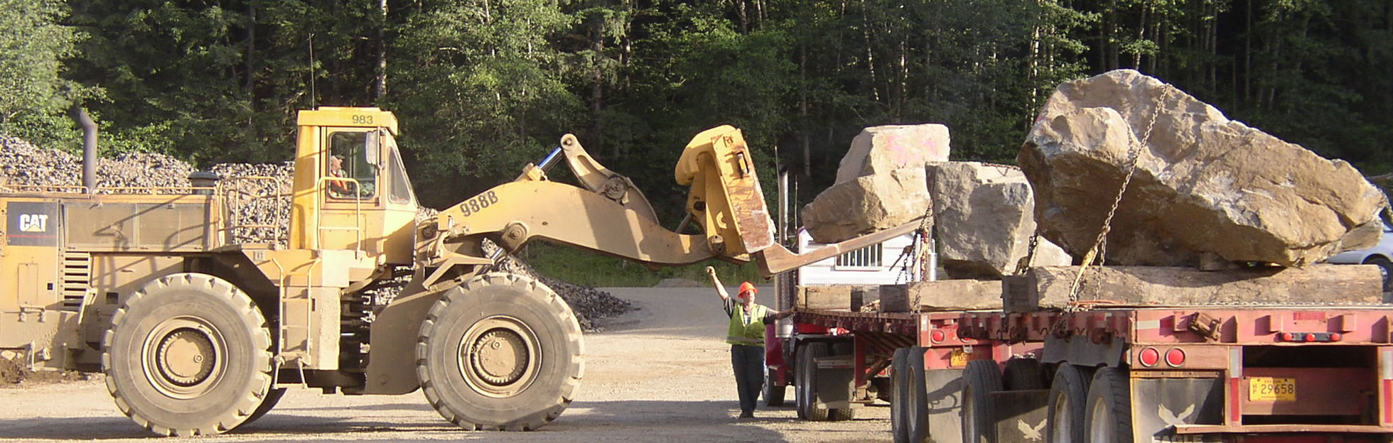articulated loader placing large rock on truck